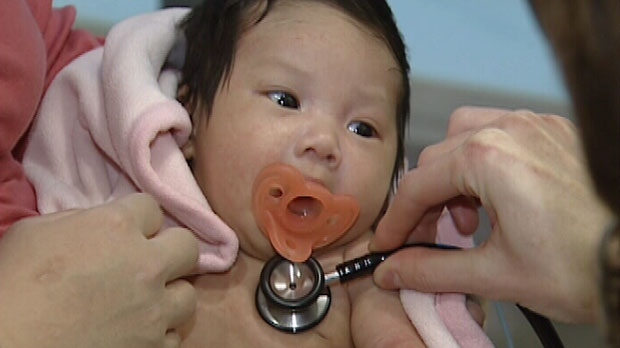 CHEO Emergency Physician checks infant for fever