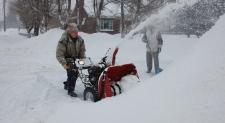 man snowblowing driveway