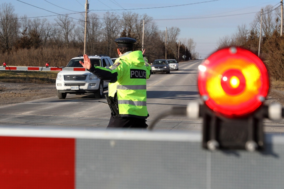A CN police officer holds traffic on CN train tracks in Tyendinaga, Ont., on Tuesday Jan. 16, 2013. Mohawk warriors blocked both the CP and the CN train tracks in support for the Idle No More movement. THE CANADIAN PRESS/Lars Hagberg