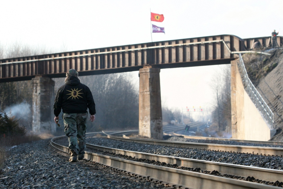 A Mohawk warrior crosses the CN and the CP train tracks crossing in Tyendinaga, Ont., on Tuesday Jan. 16, 2013. The warriors were blocking the trains tracks in support of the Idle No More movement. THE CANADIAN PRESS/Lars Hagberg