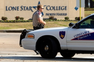 A Harris Precinct 4 Constable blocks off an entrance to the Lone Star College North Harris campus after a shooting on Tuesday, Jan. 22, 2013 in Houston. (AP Photo/Patric Schneider)