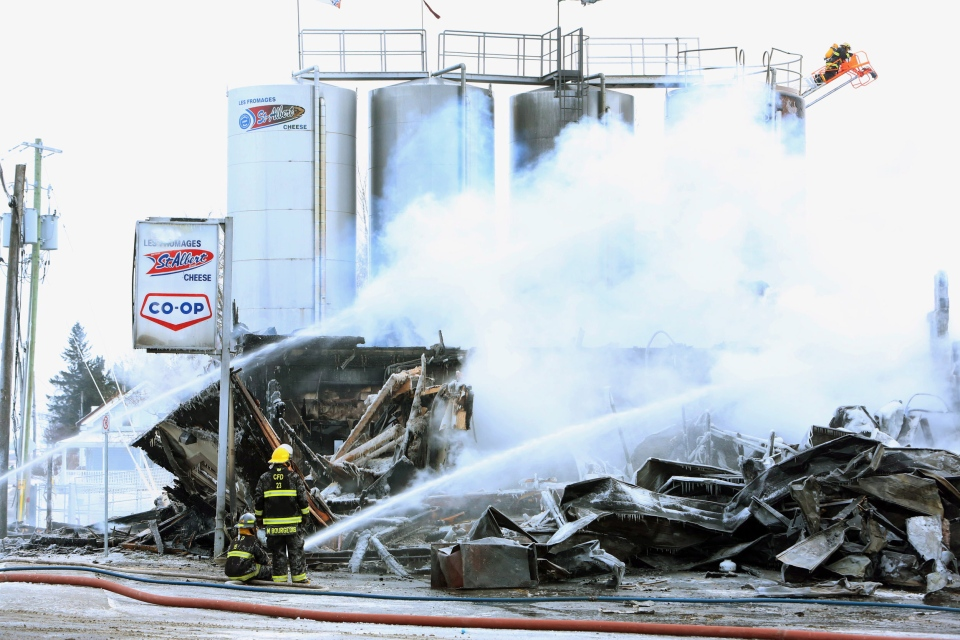 Firefighters hose down a fire at a cheese factory in St. Albert, Ontario east of Ottawa, Sunday, Feb. 3, 2013. A cheese factory east of Ottawa known for its poutine-topping curds has been gutted by a fire that broke out this morning.THE CANADIAN PRESS/Fred Chartrand
