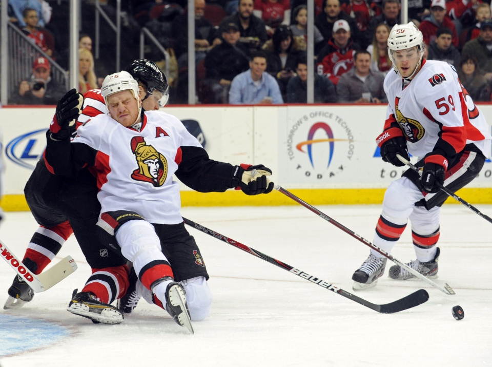 Ottawa Senators' Chris Neil, front left, reacts after being hit with the puck as he is checked by New Jersey Devils' Adam Larsson during the first period of an NHL hockey game Monday, Feb. 18, 2013, in Newark, N.J. Senators' Dave Dziurzynski, right, looks on. (AP Photo/Bill Kostroun)