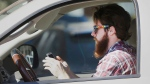 A man looks at his phone as he drives through traffic in Dallas, on Tuesday, Feb. 26, 2013. (AP / LM Otero)