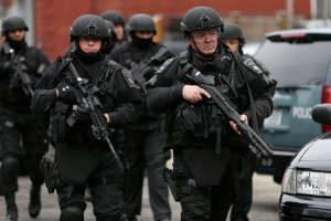 Police in tactical gear conduct a search for a suspect in the Boston Marathon bombings, Friday, April 19, 2013, in Watertown, Mass. (AP /Matt Rourke)