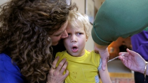 A flu vaccine is administered to Alexander Dyjak, 4, as his mother holds him during a vaccination clinic in this 2013 file photo. (Sean D. Elliot / The Day)