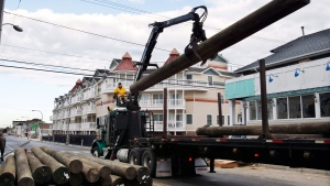 Yuri Pismennyi unloads 36 poles to be used as pilings to rebuild the boardwalk in Seaside Heights, N.J., Thursday, April 25, 2013. (AP / Mel Evans)