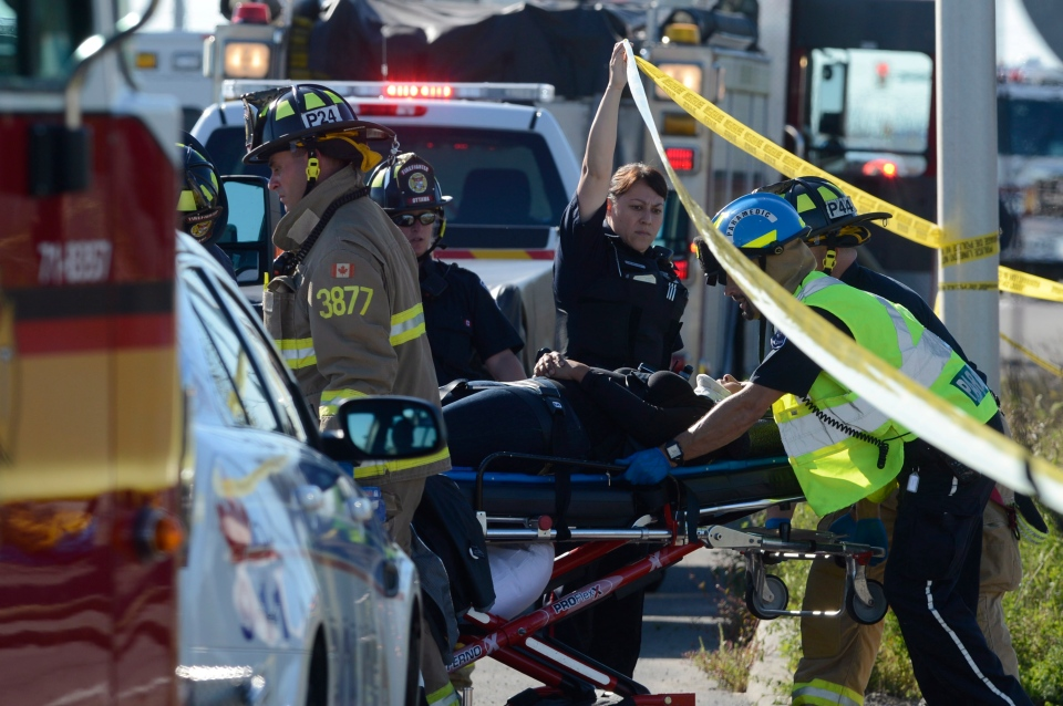A passenger is taken to an ambulance following a Via Rail train and city bus collision in Ottawa's west end Wednesday, Sept. 18, 2013. (THE CANADIAN PRESS)