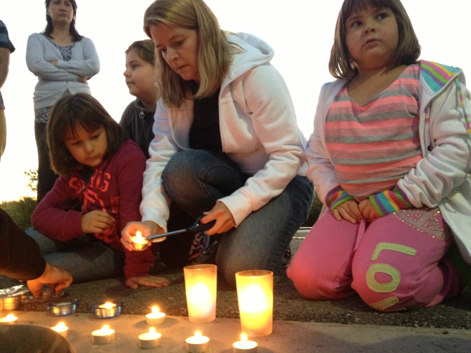 A family lights a row of candles for those who died on a horrific train crash with an OC Transpo bus on Thursday, Sept. 18, 2013.