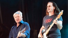 Alex Lifeson, left, and Geddy Lee of Rush, the mythic Canadian rock group, perfrom in front of close to 100,000 fans in Quebec City in July 2010. (THE CANADIAN PRESS/Jacques Boissinot)