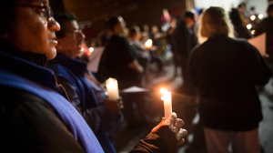 Residents attend a candlelight vigil at the West Hamilton Beach Volunteer Fire Department to commemorate the one-year anniversary of Superstorm Sandy, Monday, Oct. 28, 2013, in the Queens borough of New York. (AP Photo/John Minchillo)