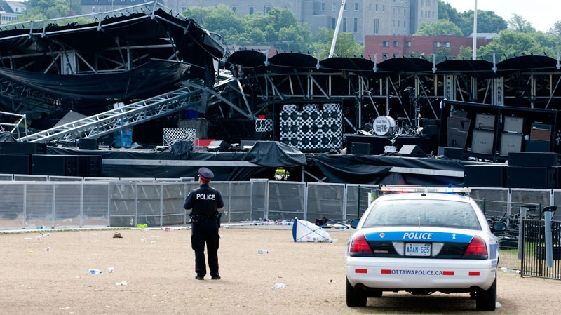 A police officer watches over the Ottawa Bluesfest's collapsed main stage  in Ottawa, Monday July 18, 2011. (Adrian Wyld / THE CANADIAN PRESS)