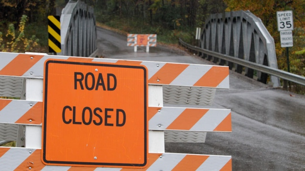 A road closed sign leading into the Muskingum County Animal Farm is shown Wednesday, Oct. 19, 2011, in Zanesville, Ohio. Police with assault rifles stalked a mountain lion, grizzly bear and monkey still on the loose after authorities said their owner apparently freed dozens of wild animals and then killed himself. (AP / Tony Dejak)
