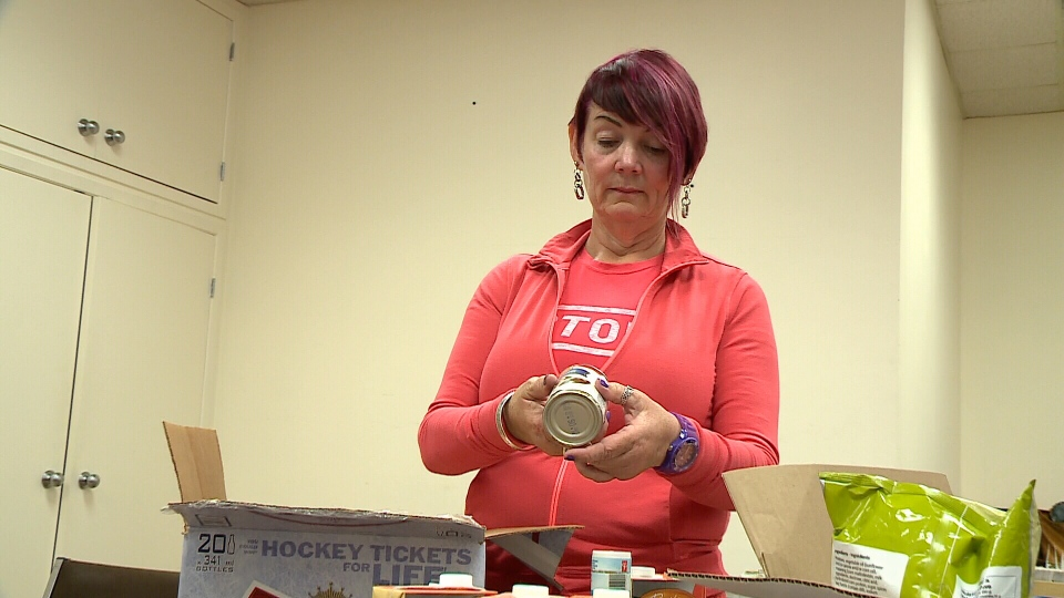 Karen Secord checks donated items at Parkdale Food Centre on Tuesday, Aug. 19, 2014.