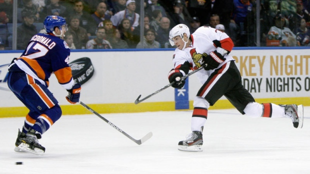 Ottawa Senators' Kyle Turris, right, takes a shot past New York Islanders' Andrew MacDonald during the third period of an NHL hockey game on Sunday, April 1, 2012, in Uniondale, N.Y. The Senators defeated the Islanders 5-1. (AP Photo/Seth Wenig)