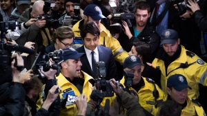 Former CBC Radio host Jian Ghomeshi, centre, is escorted out of court after being released on bail in Toronto on Wednesday, Nov. 26, 2014. (Darren Calabrese / THE CANADIAN PRESS)