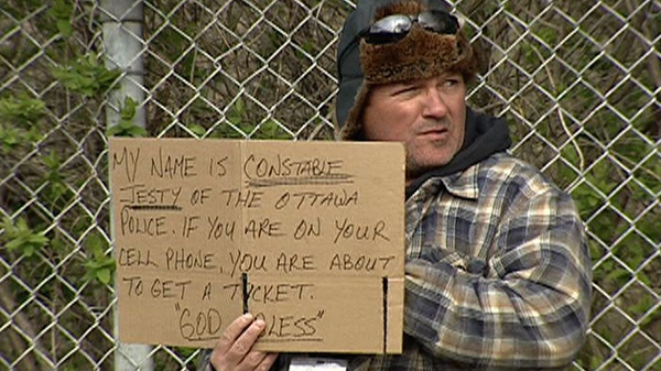 An Ottawa police officer holds a sign identifying himself as he tries to catch distracted drivers while posing as a panhandler Thursday, April 19, 2012