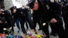 New York City police officer Darren Cox, right, accompanied by fellow officers, leaves flowers at a memorial in the Bedford Stuyvesant neighborhood of the Brooklyn borough of New York, Sunday, Dec. 21, 2014 in honor of two police officers who were shot there Saturday. (AP / Mark Lennihan)
