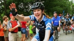 Canadian Olympic speedskater and cyclist Clara Hughes waves as she cycles with Governor General David Johnston (behind) in Arnprior Ont., in the final stretch of her Big Ride, Monday June 30, 2014. (Fred Chartrand / THE CANADIAN PRESS)