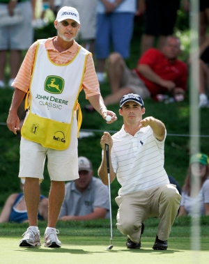 In this July 15, 2007, file photo, golfer Jonathan Byrd, right, shows caddie Mike Hicks the contour of the 17th green during John Deere Classic golf tournament at the TPC Deere Run golf course in Silvis, Ill. (AP / Charles Rex Arbogast)
