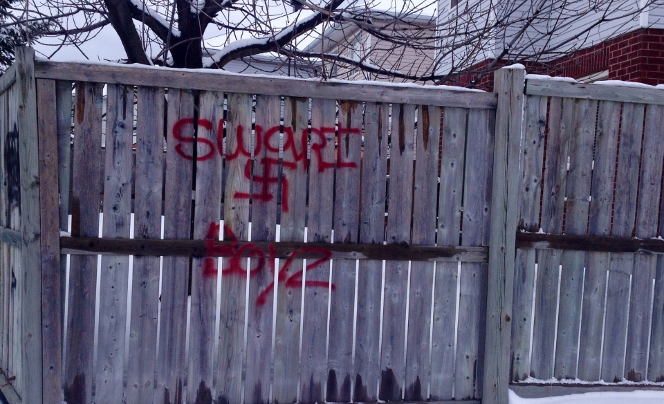 swastika and other graffiti spray painted on a wooden fence near a. Black Bedroom Furniture Sets. Home Design Ideas