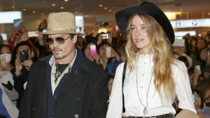 U.S. actor Johnny Depp and Amber Heard arrive at Haneda international airport in Tokyo to promote his latest film Mortdecai on Jan. 26, 2015. (AP / Shizuo Kambayashi)