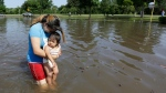 Gabby Aviles carries her daughter Audrey through floodwaters outside their apartment in Houston, Tuesday, May 26, 2015. (AP / David J. Phillip)