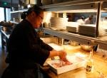 Chef Masaharu Morimoto prepares pork chops with a special Sake marinade at his restaurant Morimoto in Napa, Calif., Monday, Aug. 16, 2010. (Eric Risberg/AP Photo)