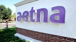 A pedestrian walks past a sign for Aetna Inc., at the company headquarters in Hartford, Conn. on Tuesday, Aug. 19, 2014, photo. (AP /Jessica Hill)