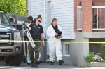 A crime scene investigator leaves a home in Boucherville, Que., on Friday, July 3, 2015, where the bodies of three men were found. (Graham Hughes/THE CANADIAN PRESS)