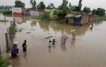 Pakistani villagers wade through floodwaters caused by heavy rains at a village on the outskirts of Nowshera near Peshawar, Pakistan, Sunday, Aug. 2, 2015. (AP/Muhammad Sajjad)