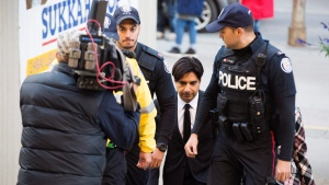 Former CBC radio host Jian Ghomeshi, centre, arrives to appear for a pre-trial hearing for his sexual assault case, in Toronto, on Thursday, October 1, 2015. (THE CANADIAN PRESS/Michelle Siu)