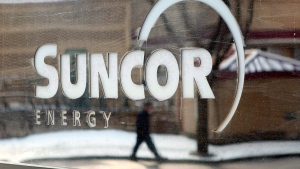 A pedestrian is reflected in a Suncor Energy sign in this file photo taken in Calgary on Feb. 1, 2010. (Jeff McIntosh/THE CANADIAN PRESS)