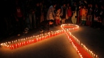 """Nepalese women and children from """"Maiti Nepal"""", a rehabilitation center for victims of sex trafficking, light candles on the eve of World AIDS Day in Kathmandu, Nepal, Monday, Nov. 30, 2015. (AP Photo/Niranjan Shrestha)"""