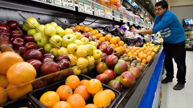 Grocery store owner Gilles Robin works on his fruits vegetable display Tuesday Nov. 28 2006 in the Breakeyville, a suburb of Levis Que. (CP PHOTO/Jacques Boissinot)