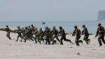 U.S. and Philippine marines storm the beach to simulate a raid during the joint military exercise at the Naval Training Exercise Command, northwest of Manila, Philippines, on Friday, May 9, 2014. (AP Photo/Bullit Marquez)