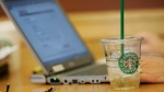 An iced drink sits next to a laptop computer at a Starbucks Corp. store near the University of Washington in Seattle, on Feb. 11, 2008. (Ted S. Warren / AP)
