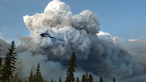 A helicopter flies past a wildfire in Fort McMurray, Alta., on Wednesday May 4, 2016. (Jason Franson / THE CANADIAN PRESS)