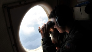 U.S. Navy LT. JG Dylon Porlas uses binoculars to look through the window of a U.S. Navy Lockheed P-3C Orion patrol aircraft from Sigonella, Sicily, Sunday, May 22, 2016, searching the area in the Mediterranean Sea where the Egyptair flight 804 en route from Paris to Cairo went missing on May 19.  (AP Photo/Salvatore Cavalli)