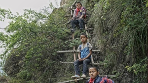 Children carrying their schoolbags take a rest on the ladder built on a cliff in Zhaojue county, southwest China's Sichuan province on May 14, 2016. (Chinatopix)
