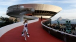 A model walks down a ramp of the Contemporary Art Museum wearing a creation from the Louis Vuitton Cruise 2017 collection, in Niteroi, Brazil, Saturday, May 28, 2016. (AP Photo / Leo Correa)