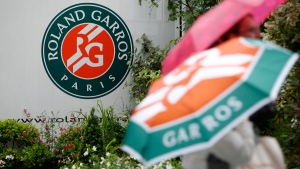 People walk by the Roland Garros stadium logo at the French Open tennis tournament, May 30, 2016 in Paris. (Alastair Grant / AP)