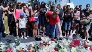 A woman puts flowers near the scene where a truck mowed through revelers in Nice, southern France, Friday, July 15, 2016. A large truck mowed through revelers gathered for Bastille Day fireworks in Nice, killing more than 80 people and sending people fleeing into the sea as it bore down for more than a mile along the Riviera city's famed waterfront promenade. (AP Photo/Francois Mori)