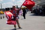 A street vendor sells flags, some showing Turkish President Recep Tayyip Erdogan in central Istanbul, Thursday, July 21, 2016. (AP Photo/Petros Giannakouris)