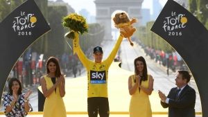 2016 race winner Britain's Chris Froome, wearing the overall leader's yellow jersey, holds the trophy aloft from the podium after the twenty-first stage of the Tour de France cycling race in Paris, France, Sunday, July 24, 2016. (Stephane Mantey Pool via AP)