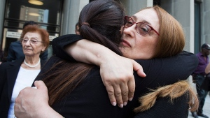 Sammy Yatim's mother Sahar Bahadi embraces her daughter Sarah at a Toronto courthouse after the sentencing of Const. James Forcillo in Toronto on Thursday, July 28, 2016. (Michelle Siu / THE CANADIAN PRESS)