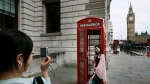 Tourists take pictures of each other with a traditional red telephone booth in central London, Thursday, Aug. 28, 2008. (AP Photo/Lefteris Pitarakis)
