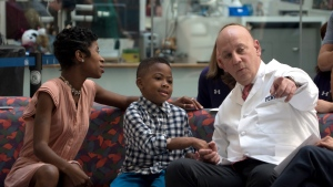 Zion Harvey, center, who received a double hand transplant in July 2015, sits next to his mother Pattie Ray, left, and holds hands with one of his surgeons, L. Scott Levin, right, during a news conference Tuesday, Aug. 23, 2016 at The Children's Hospital of Philadelphia in Philadelphia. (AP / Dake Kang)