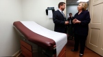 Democratic presidential candidate Hillary Clinton listens to Dr. Christopher Beckett, CEO of Williamson Health and Wellness Center, during a tour of an exam room in Williamson, W.Va. in this May 2, 2016 file photo. President Barack Obama's health care law is struggling in many parts of the country. The question is: what can Clinton do about it? (Paul Sancya/THE ASSOCIATED PRESS)
