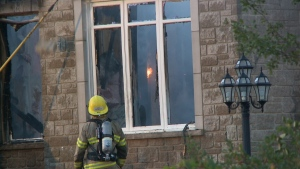 A firefighter watches as flames are seen through the window of a house in Chelsea, QC on Wednesday, Set. 21, 2016. (CTV Ottawa)